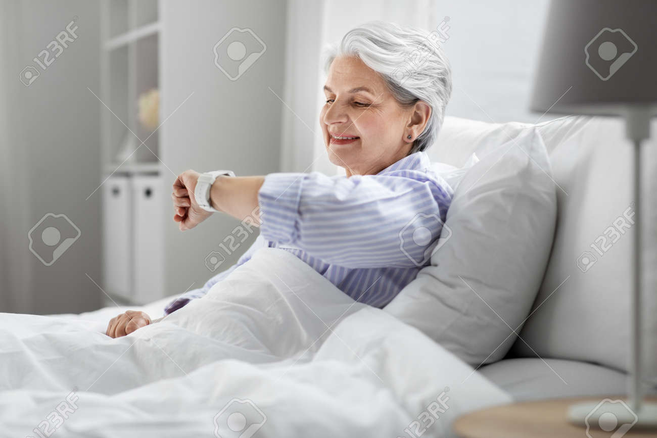 happy senior woman sitting in bed at home bedroom - 169967072