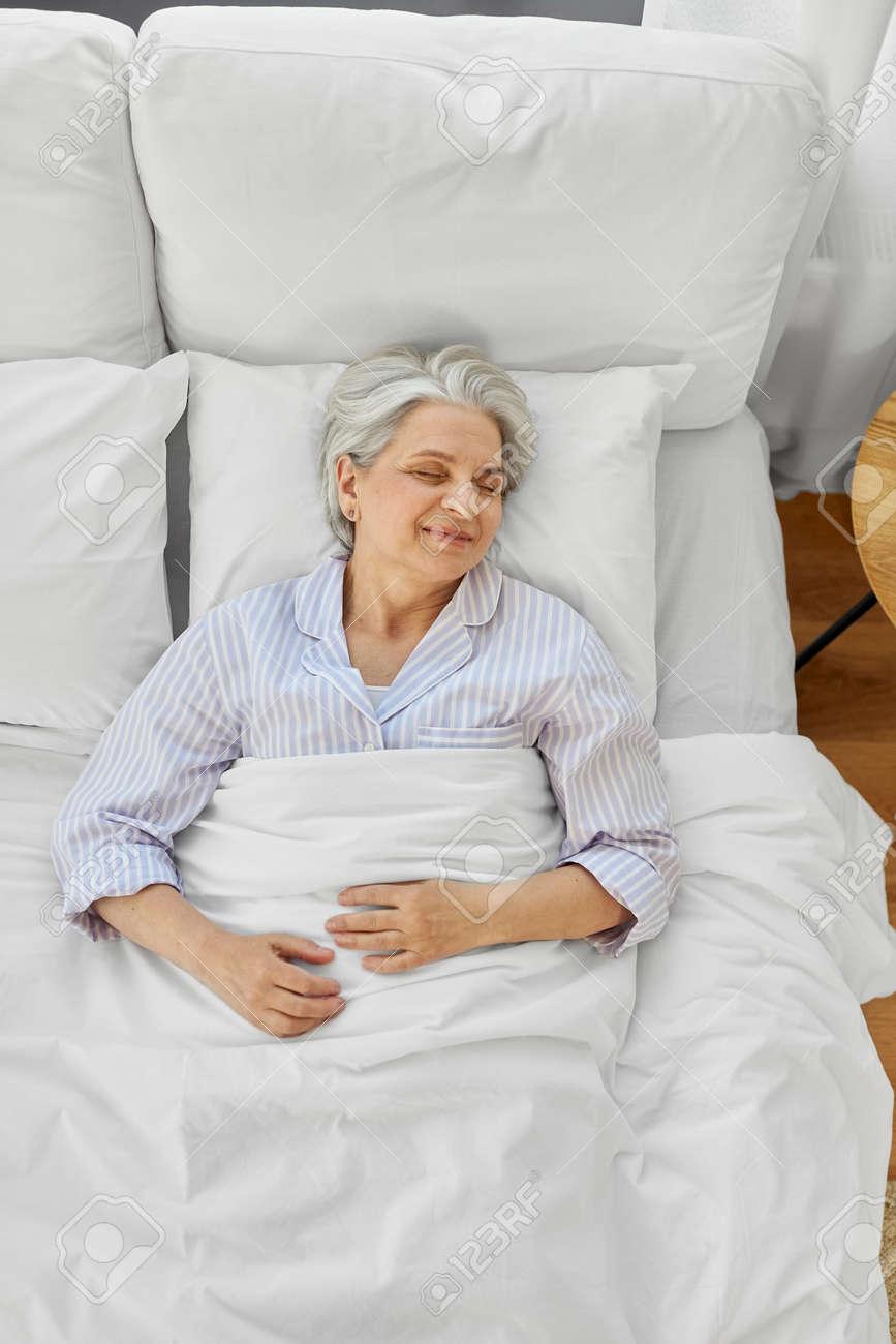 happy senior woman sleeping in bed at home bedroom - 169967556