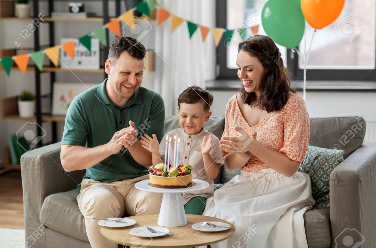 happy family with birthday cake at home - 169966360