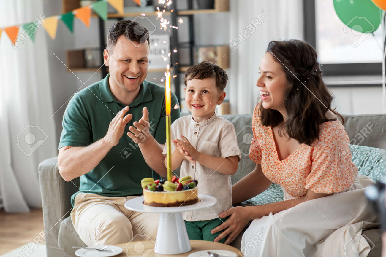 happy family with birthday cake at home - 169966406