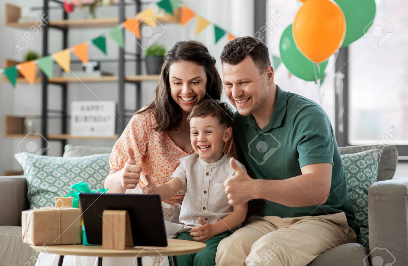 family with tablet pc has video call on birthday - 169968231
