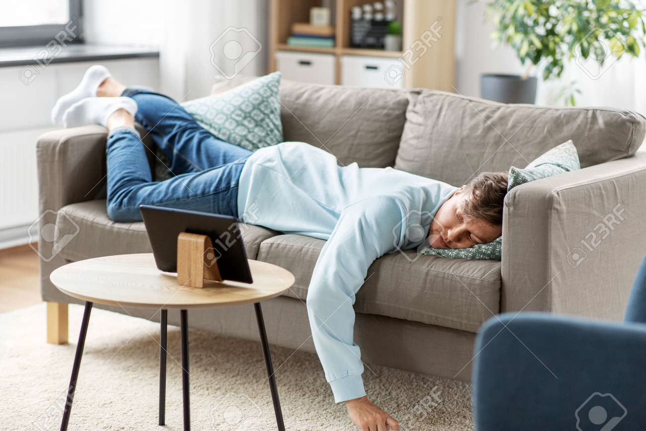 bored man with tablet pc lying on sofa at home - 169966641