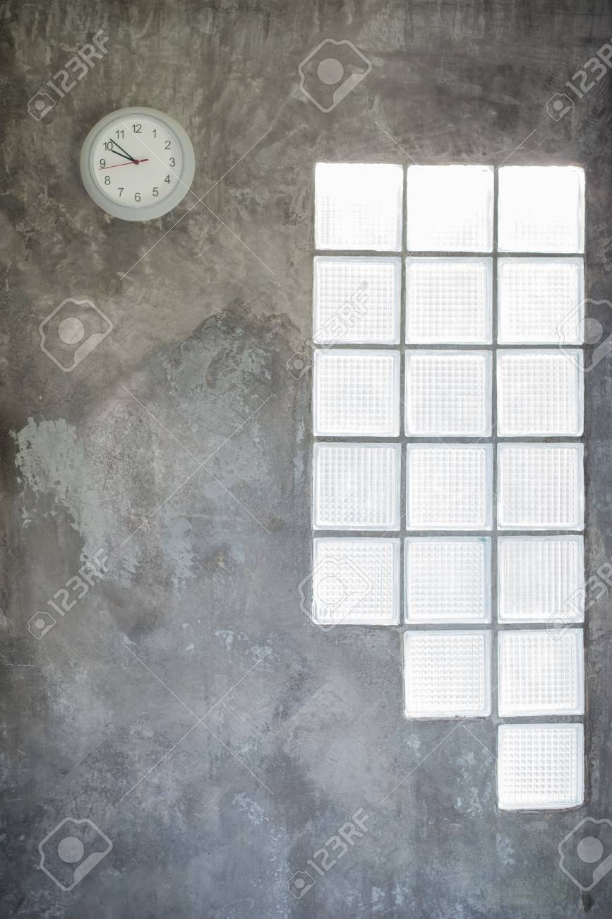 Clock Hanging On The Cement Wall And Glass Window Stock Photo