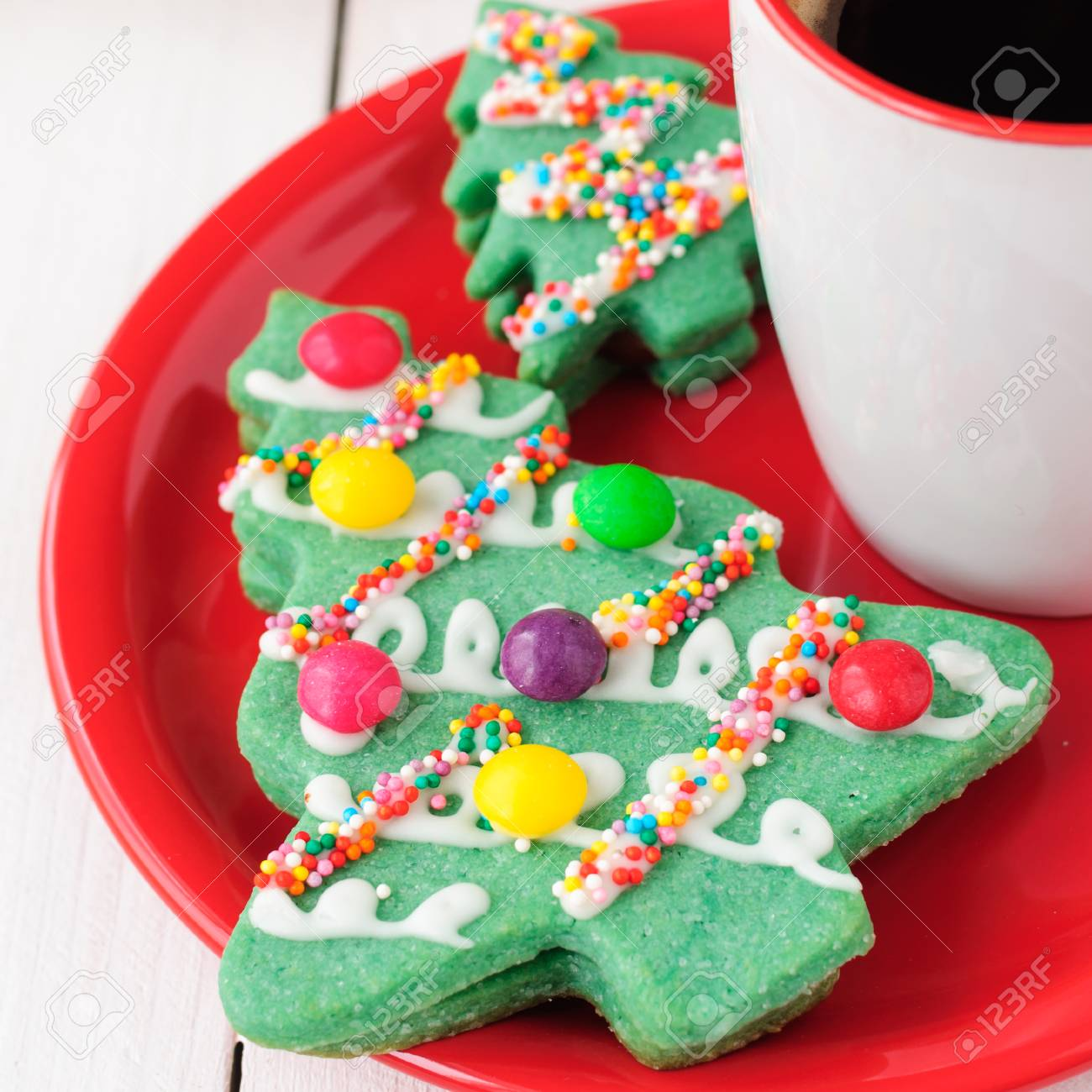 Christmas Tree Cookies On A Red Plate With A Cup Of Coffee Stock ...
