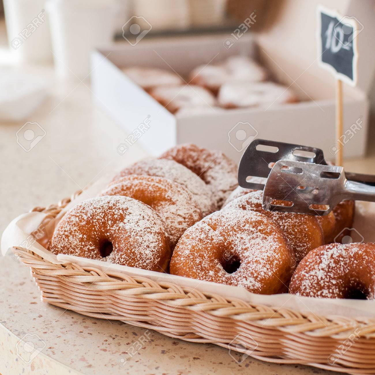 doughnut store counter donuts with icing sugar in a display stock