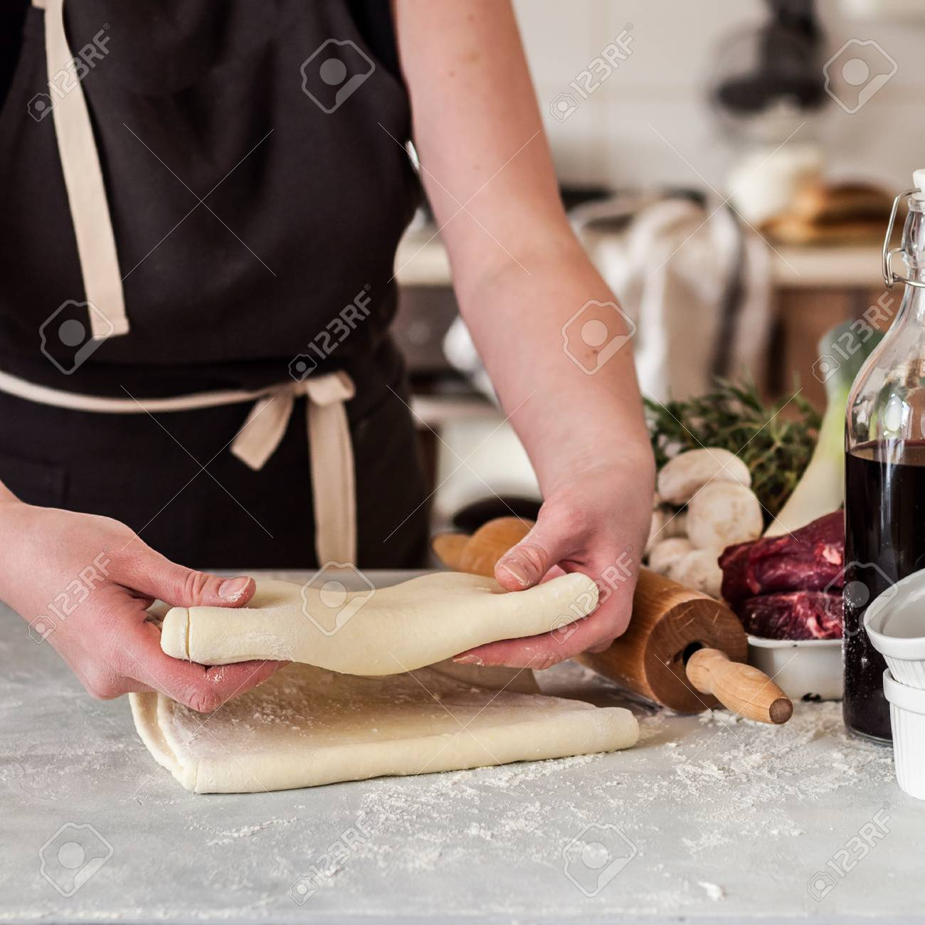 A Woman Making Puff Pastry Dough for Meat Pies, square Stock Photo - 94735056