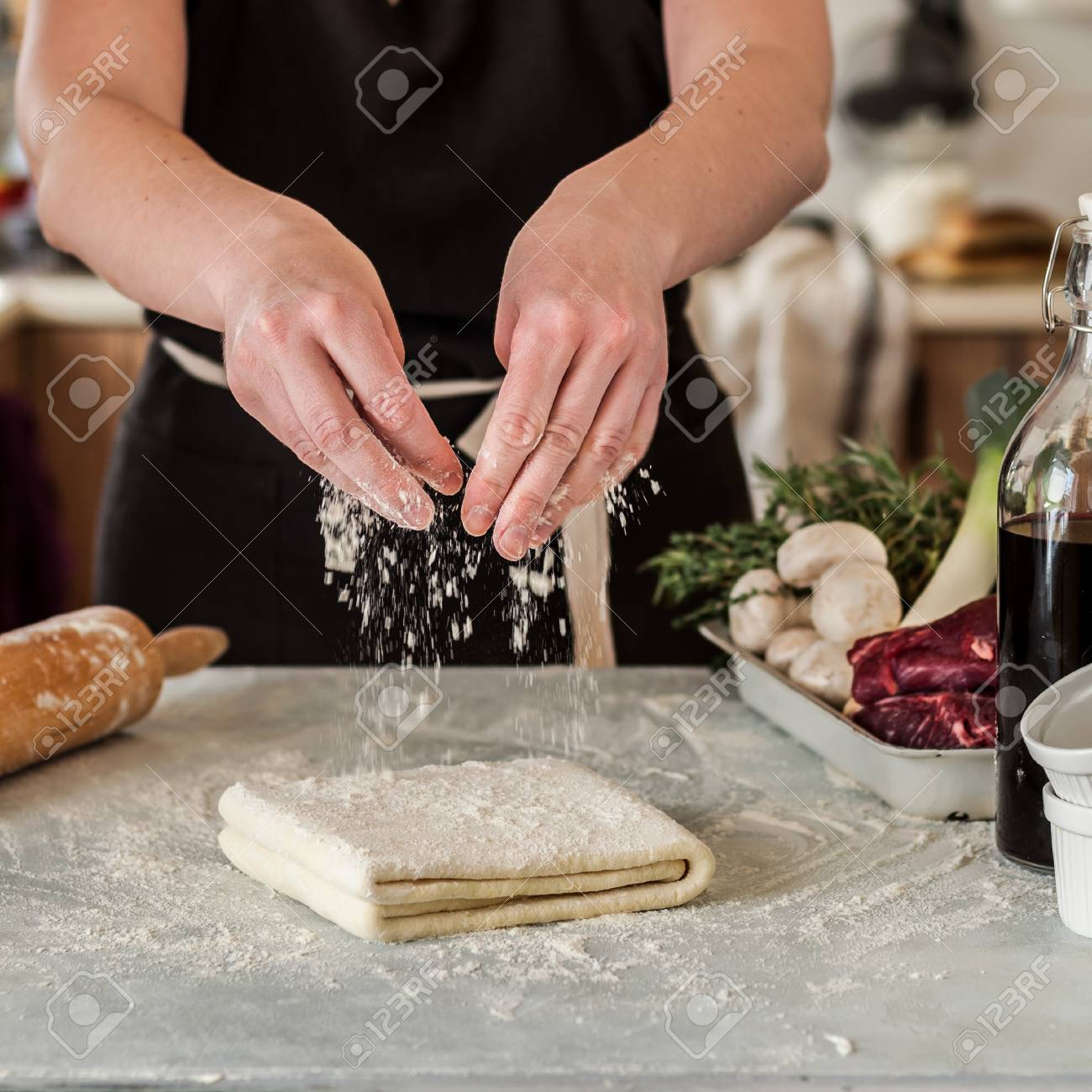 A Woman Making Puff Pastry Dough for Meat Pies, square Stock Photo - 99036743