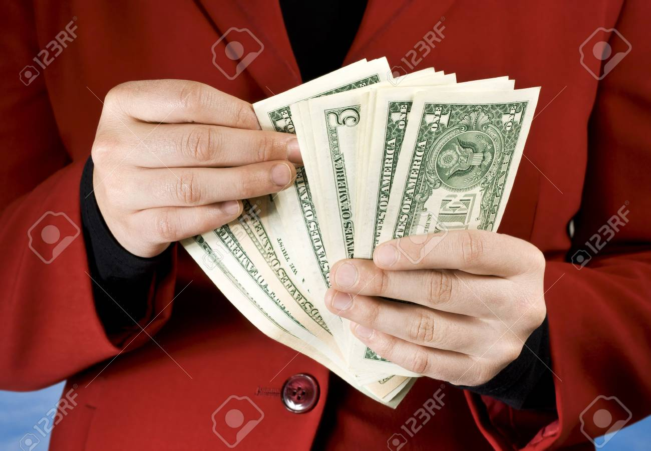 Female dressed in a red business dress using hands to count American dollars.Studio shot. Stock Photo - 2297064