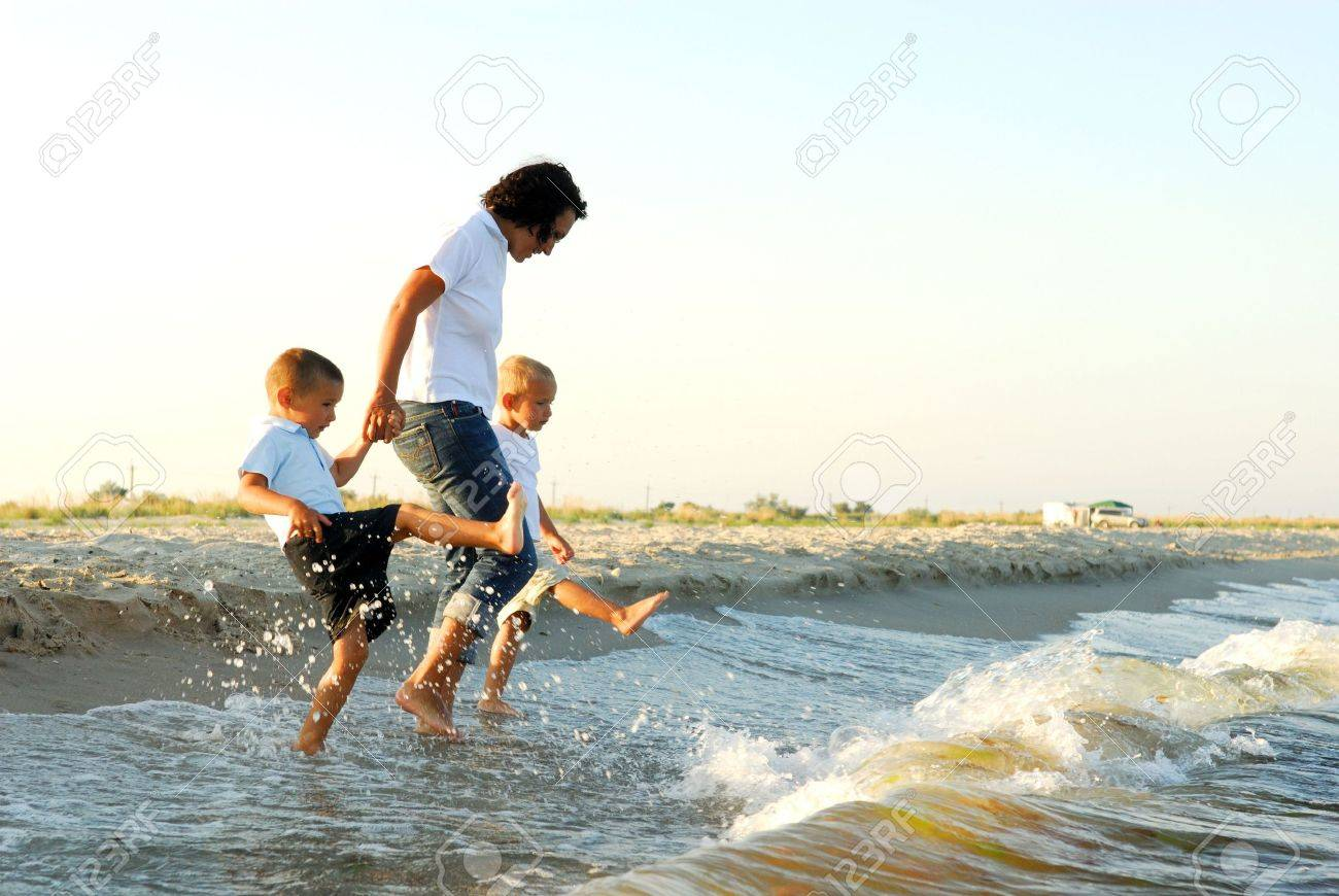 Partial profile of a woman holding the hands of two young boys, as they splash their feet in shallow water ahead of oncoming waves. Stock Photo - 3709658