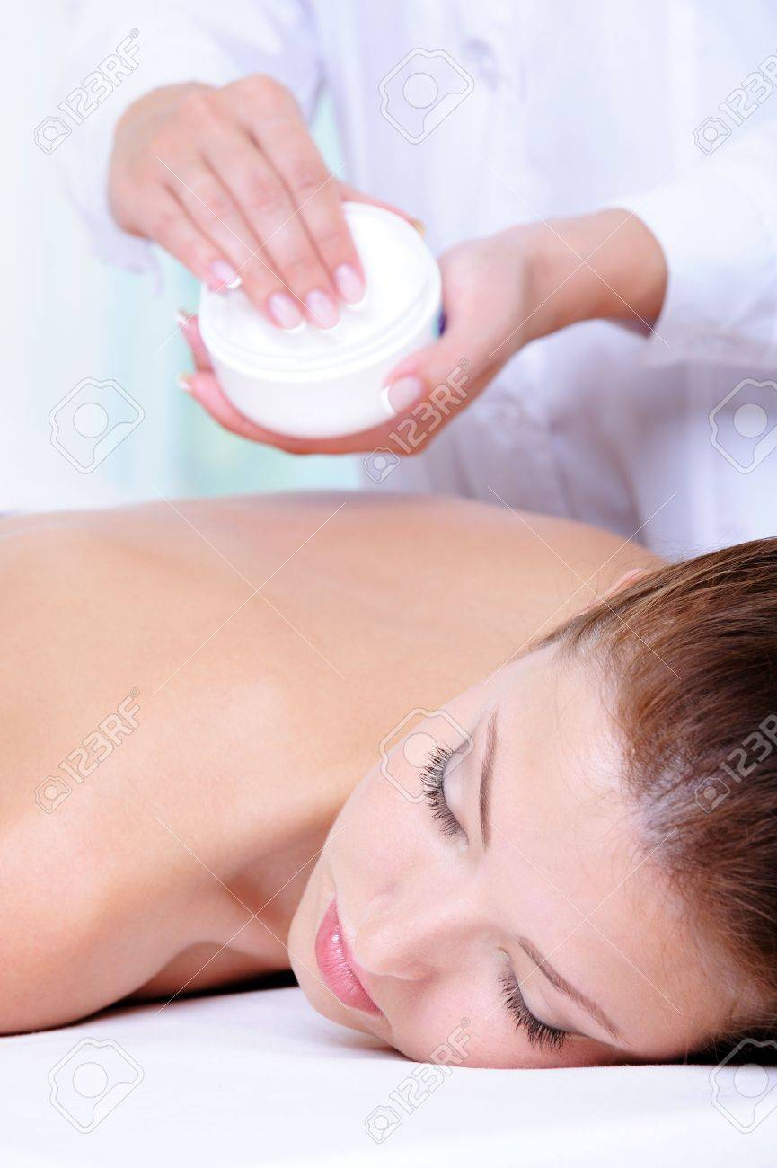 Applying  moisturizing  cream for the back massage by beautician - colored background Stock Photo - 5248940