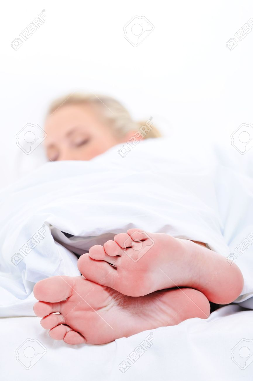 On foreground close-up  clean feets of a pretty woman sleep cover the white blanket Stock Photo - 5671284