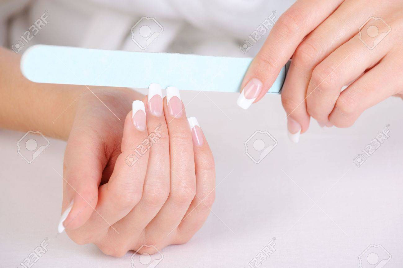 Female polishing her fingernails with a french manicure Stock Photo - 5859104