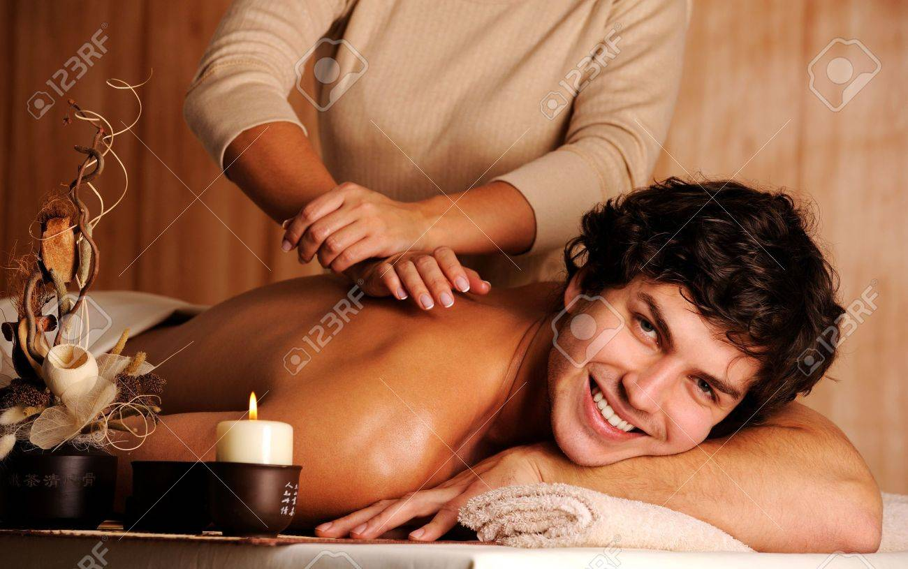 Masseur doing massage a handsome happy young man Stock Photo - 5878909