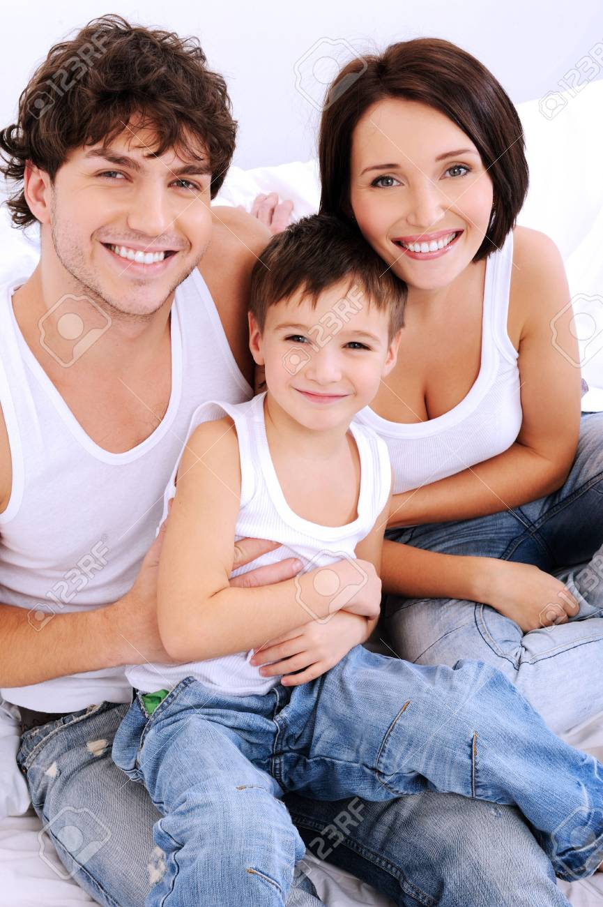 High angle portrait of the happy family looking at camera sitting on a bed Stock Photo - 6068251