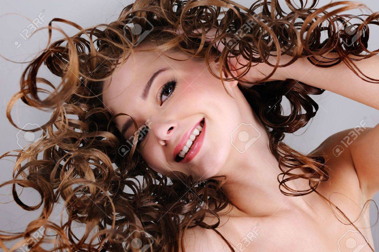 Low angle portrait of the cheerful smiling woman with long curly hairs Stock Photo - 6121706