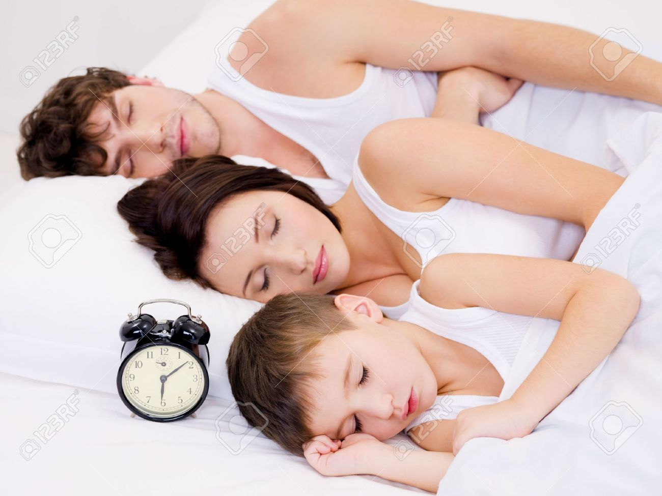 Three person of the young family sleeping with alarm clock near  their  heads Stock Photo - 6614546