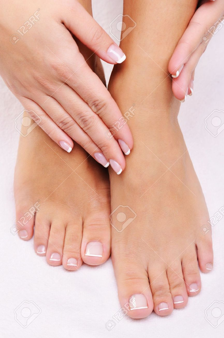 beautiful care female feet with the hand with a french manicure