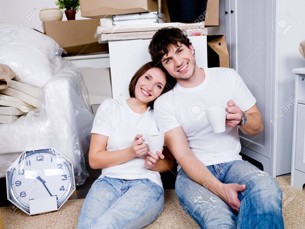 Happy people sitting on the floor with cups of tea after removing in the new home and relax Stock Photo - 6808980