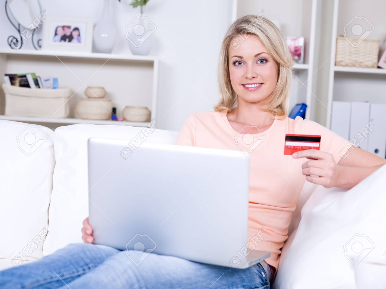 Beautiful smiling young woman with laptop holding credit card Stock Photo - 6808970