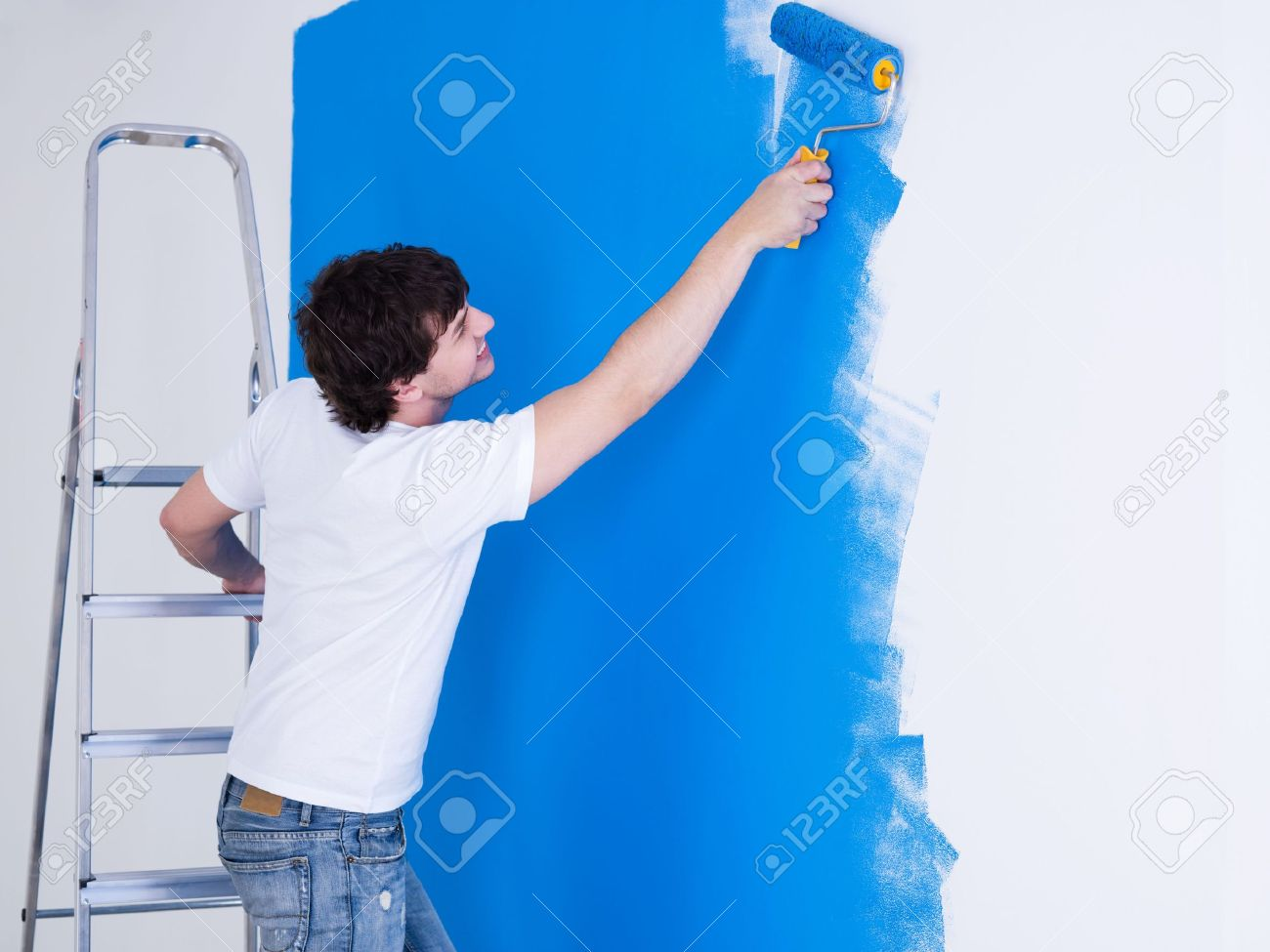 Person painting wall - Handsome Young Man Painting The Wall In Blue Horizontal Stock Photo 6870041
