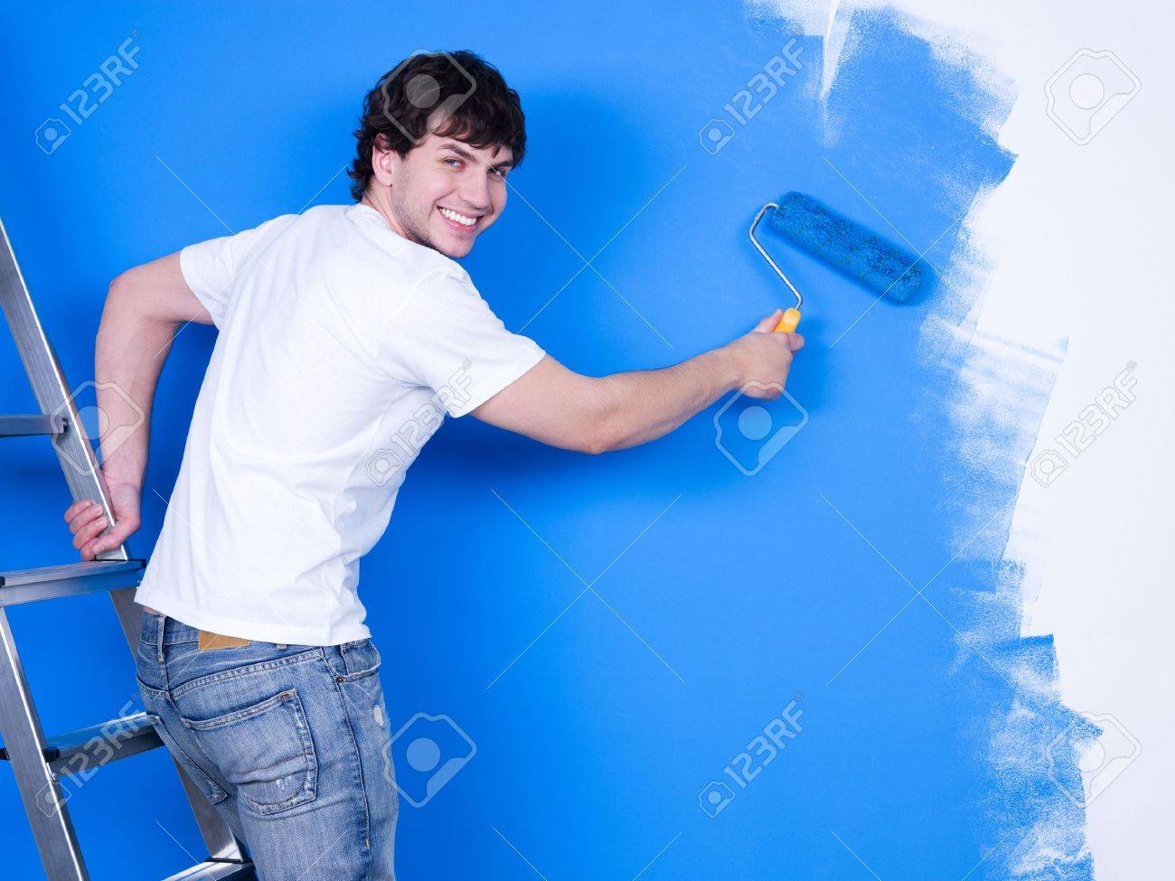 Person painting wall - Painting Wall Handsome Young Man With Happy Smile Painting The Wall