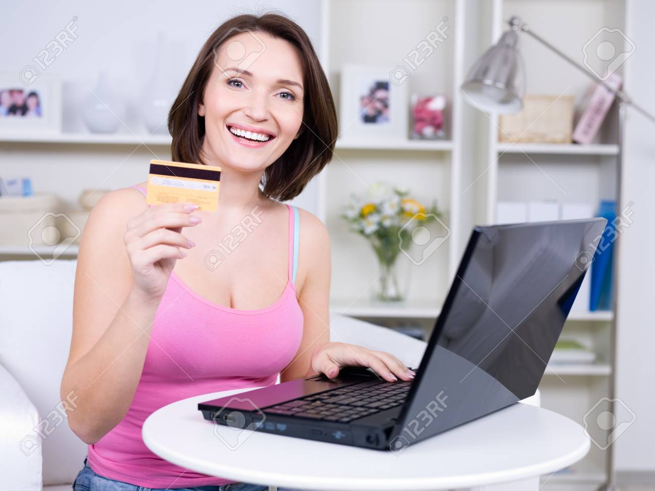 Portrait of happy young beautiful woman holding credit card and using laptop Stock Photo - 7058166