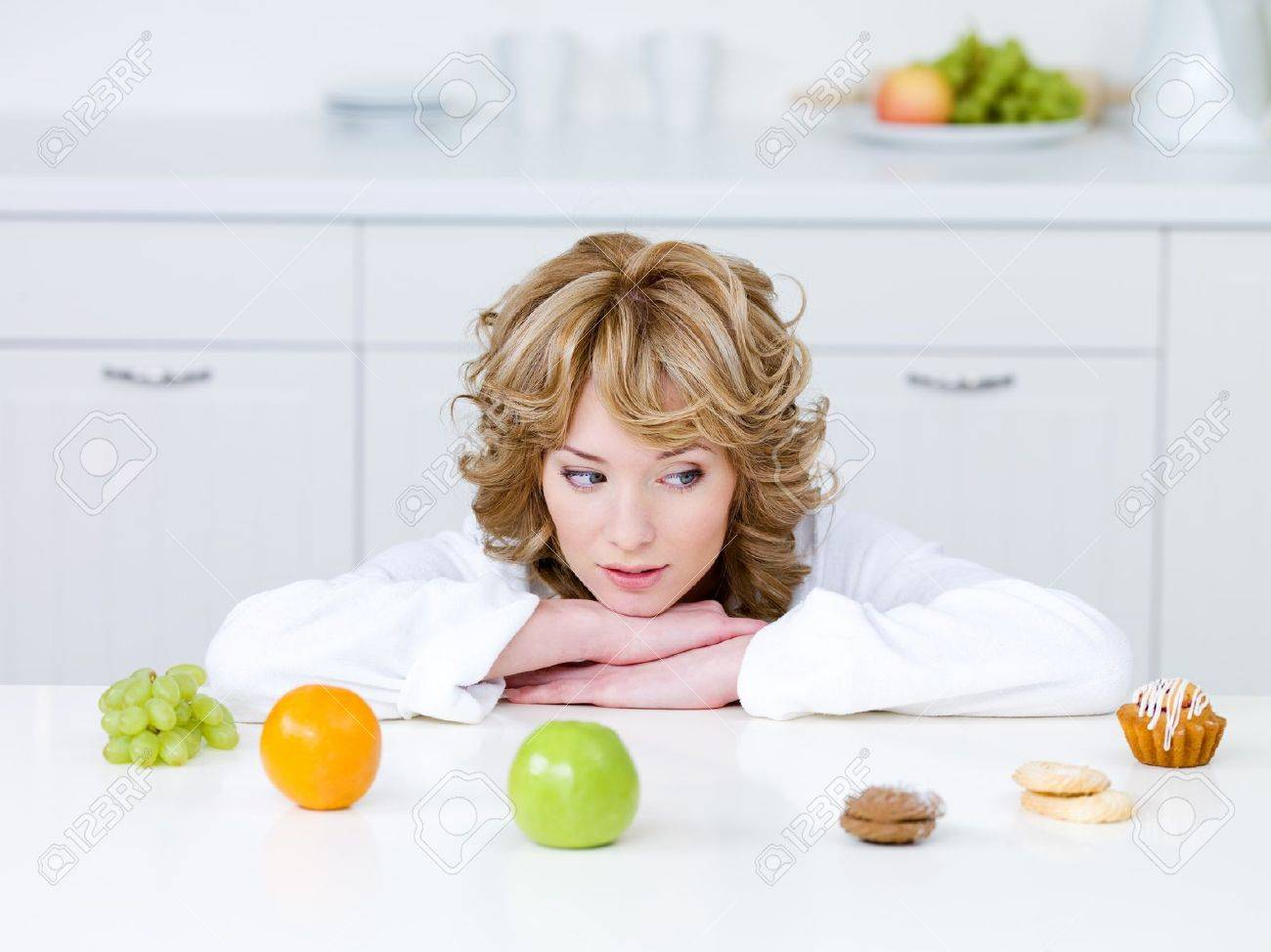 Beautiful young woman sitting in the kitchen and choosing between healthy fruits and tasty cakes - 7284258