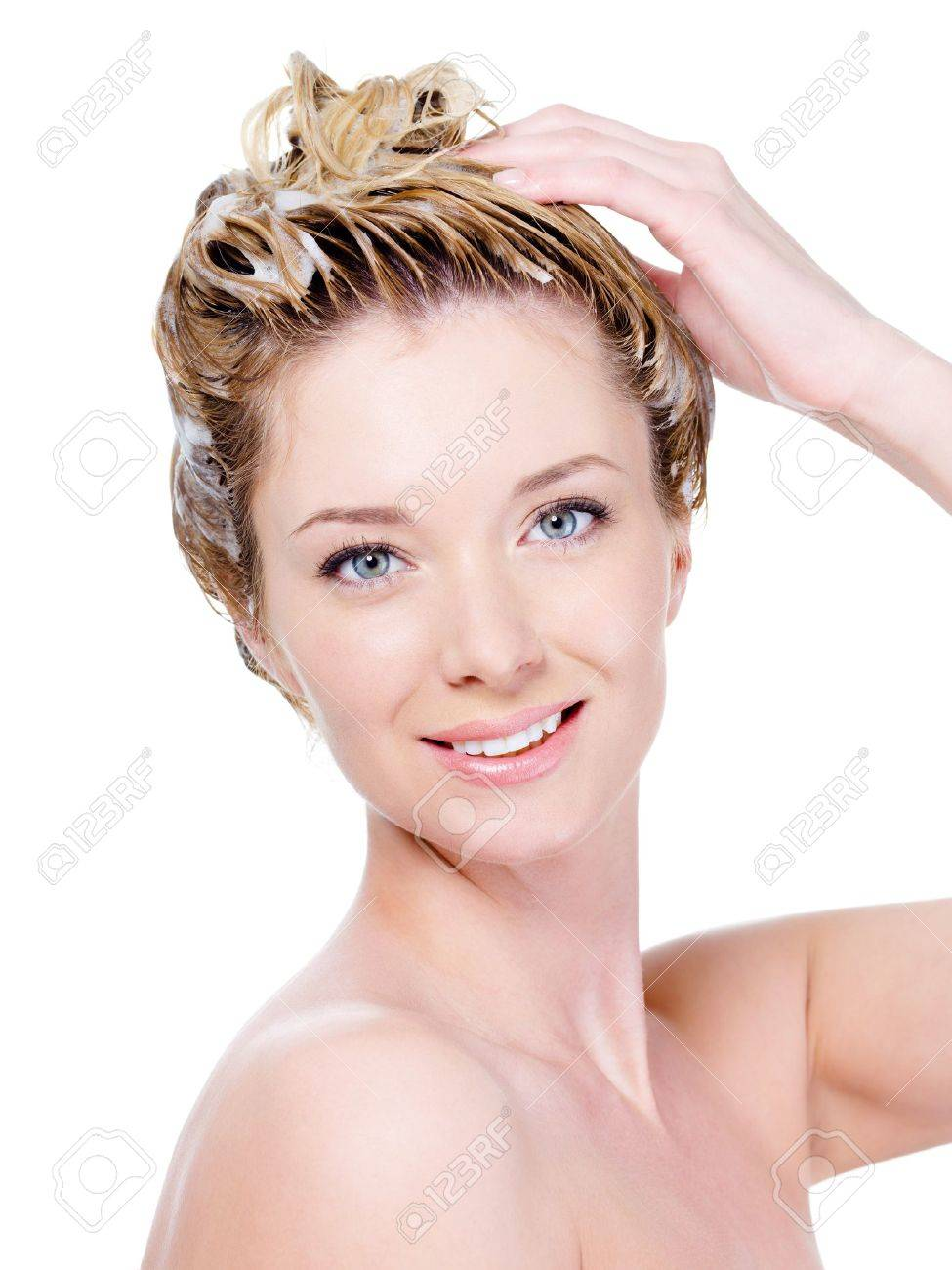 Portrait of beautiful young smiling woman washing her hair - isolated on white Stock Photo - 7337529