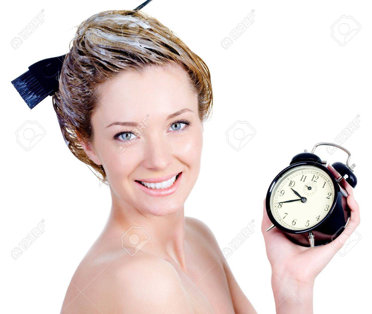 Close-up portrait of beautiful young woman with attractive smile coloring hair and holding alarm - isolated Stock Photo - 7337512