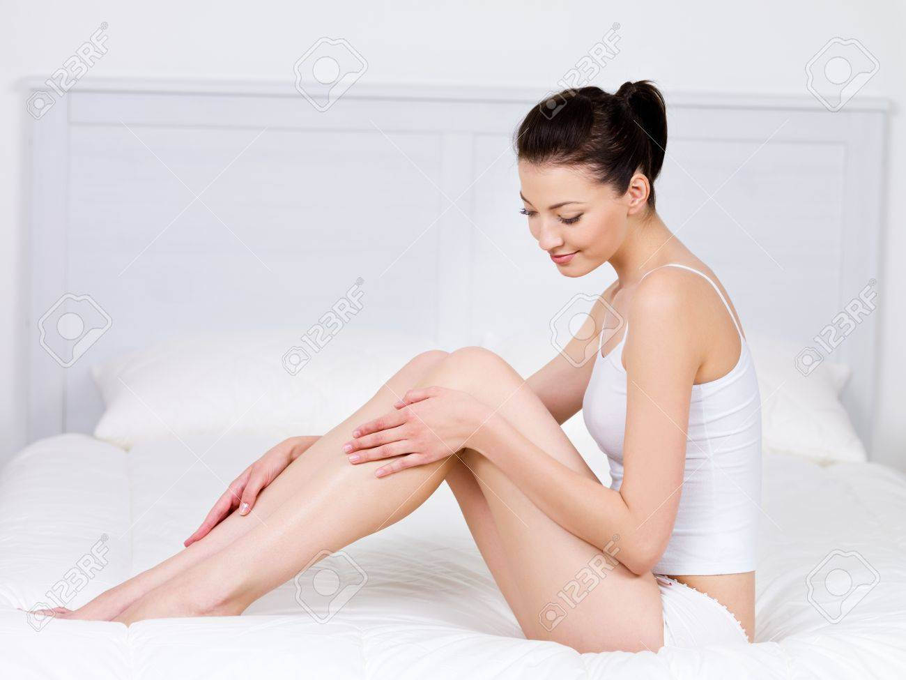 Beautiful young woman sitting on a bed and stroking her perfect legs - indoors Stock Photo - 7337564