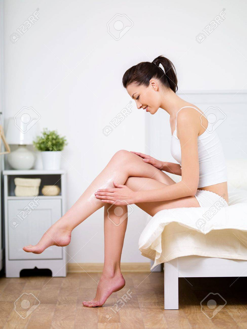 Caring about woman's leg with moisturizing cream by young beautiful woman sitting on a bed at home Stock Photo - 7337577