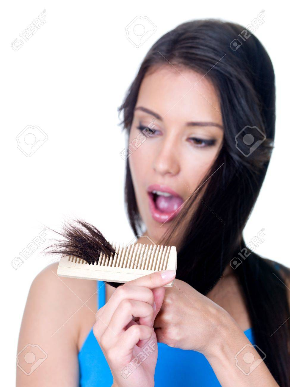 Horror on the face of young woman looking at the unhealthy ends of hair - isolated Stock Photo - 7337581
