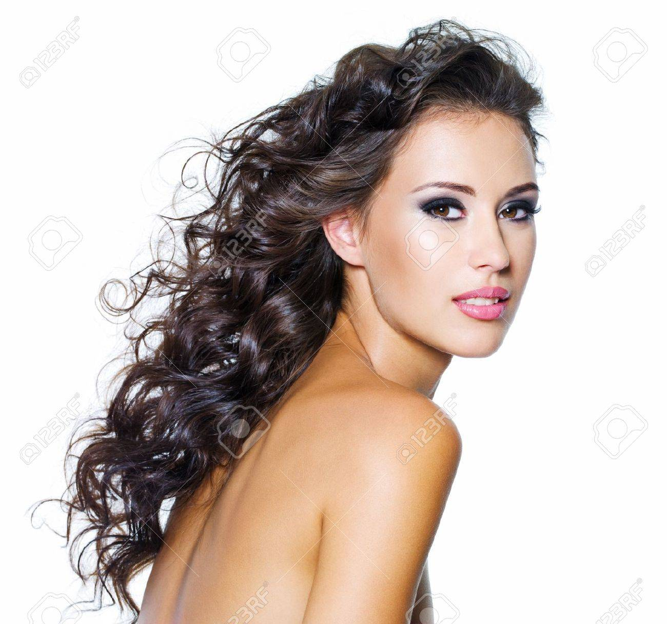 Beautiful face of young woman with clean skin. Girl with long curly hairs. Bright eye make-up Stock Photo - 7506945