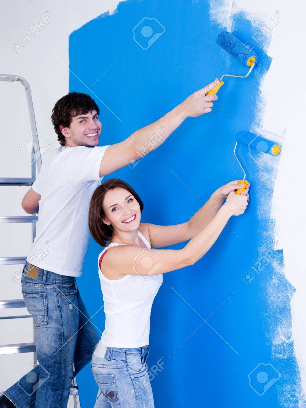 Portrait of happy smiling couple brushing the wall - indoors Stock Photo - 7917544