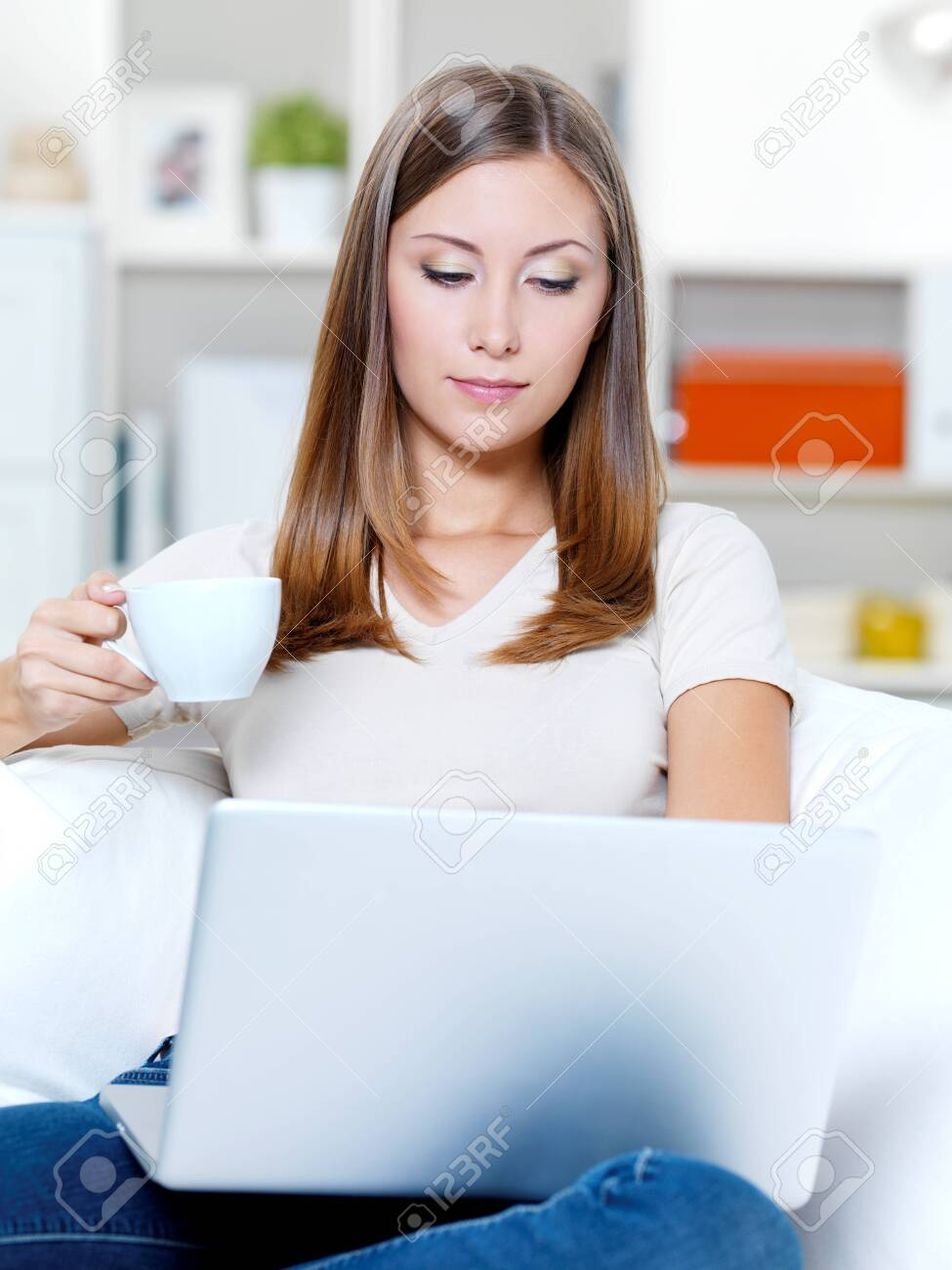 Beautiful young serious woman with laptop and cup of coffee on the sofa Stock Photo - 8041211