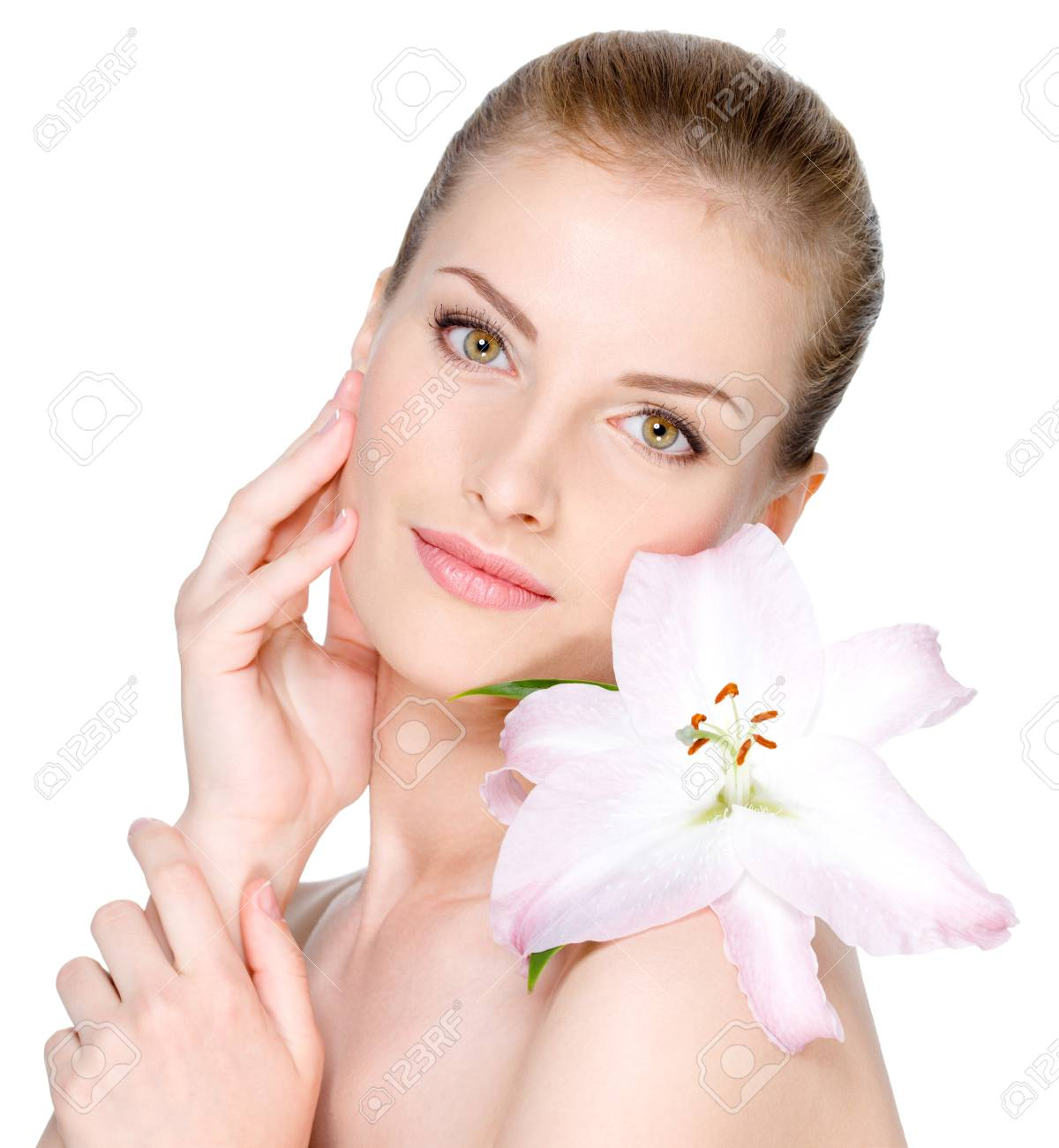 Beautiful young woman with flower on a shoulder stroking her clear face - isolated on white Stock Photo - 8078631