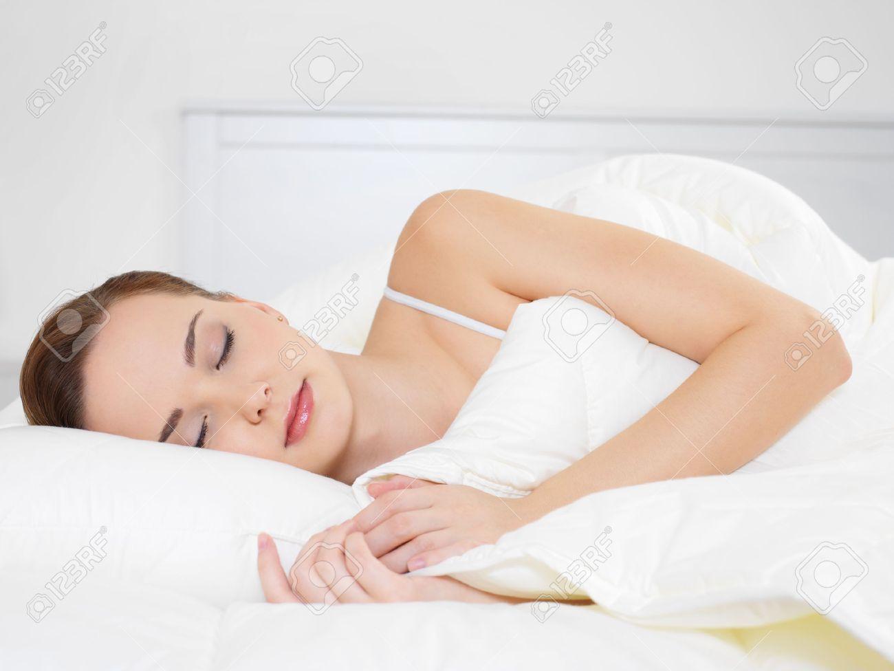 Young beautiful woman sleeping lying on the side in the bedroom Standard-Bild - 8347442