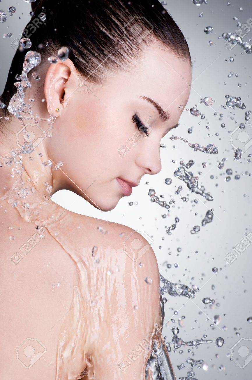 Splashes and drops of water around the female face with clean skin - vertical Stock Photo - 9195357