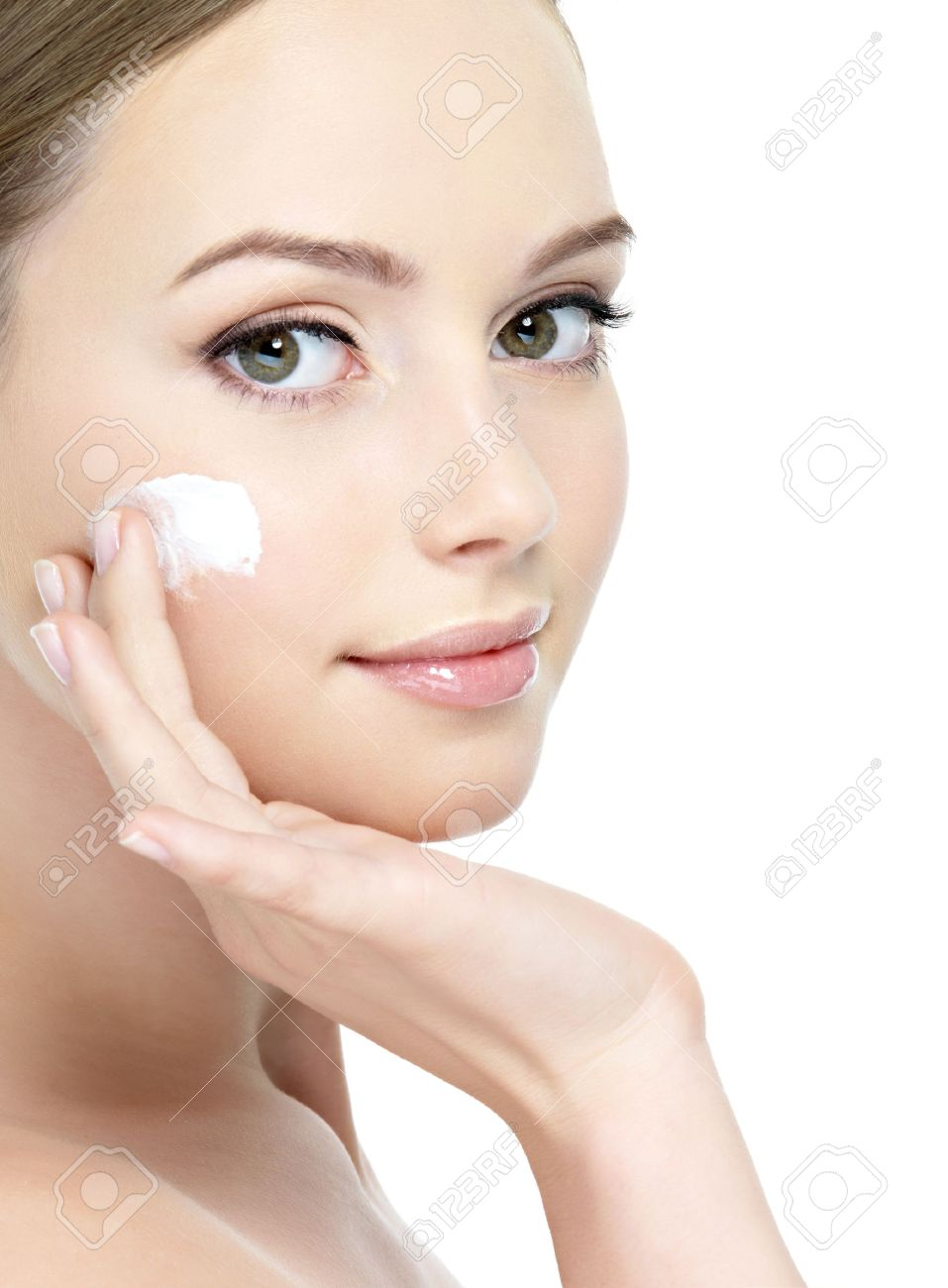 Close-up young beautiful face of girl applying moisturize cream - isolated Stock Photo - 9244621