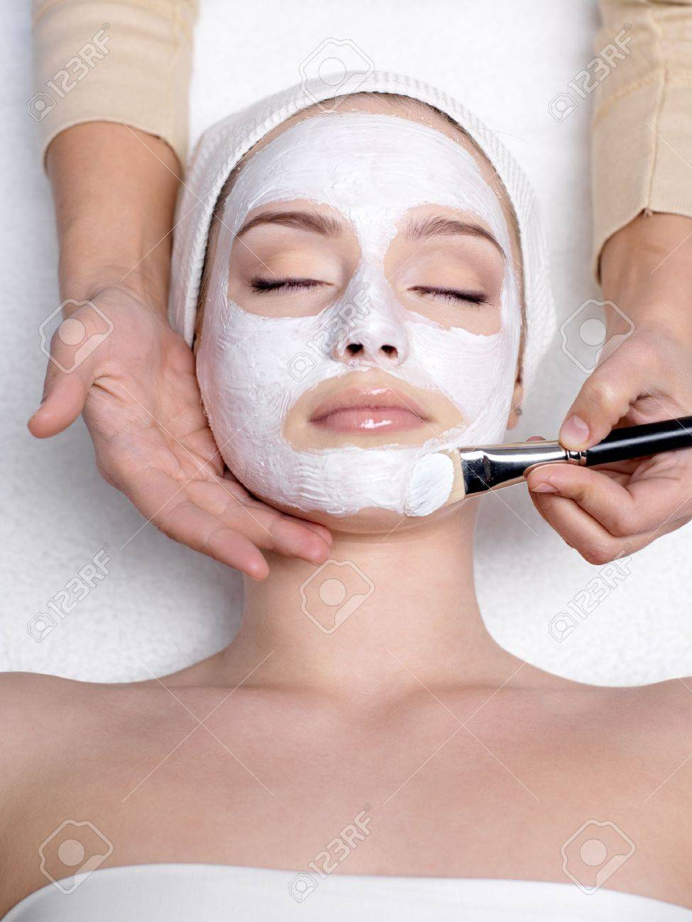 Cosmetician apllying facial mask to the face of young beautiful woman in spa salon - vertical Stock Photo - 9244676