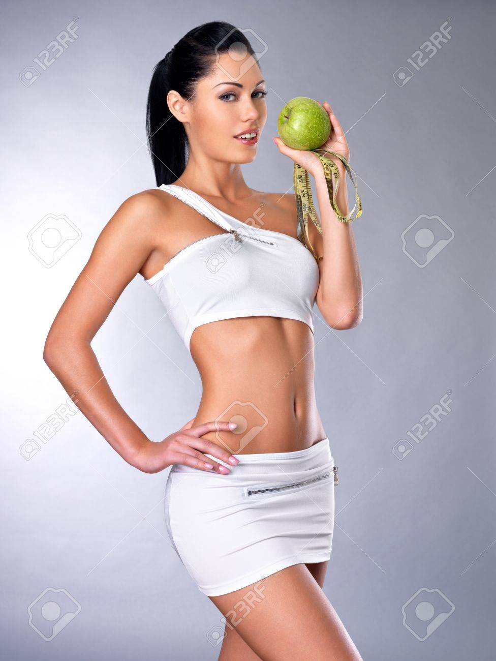 Portrait of a healthy woman with apple and bottle of water. Healthy fitness and eating lifestyle concept. Stock Photo - 16300958