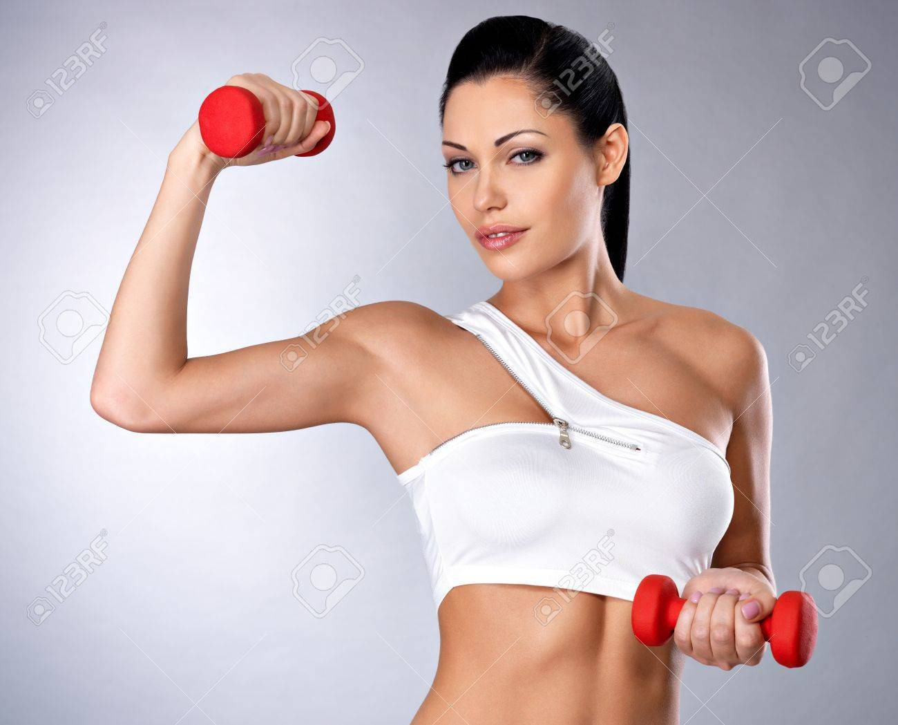 Portrait of beautiful young woman with dumbbells -  grey studio background. Healthy lifestyle concept. Stock Photo - 16300972