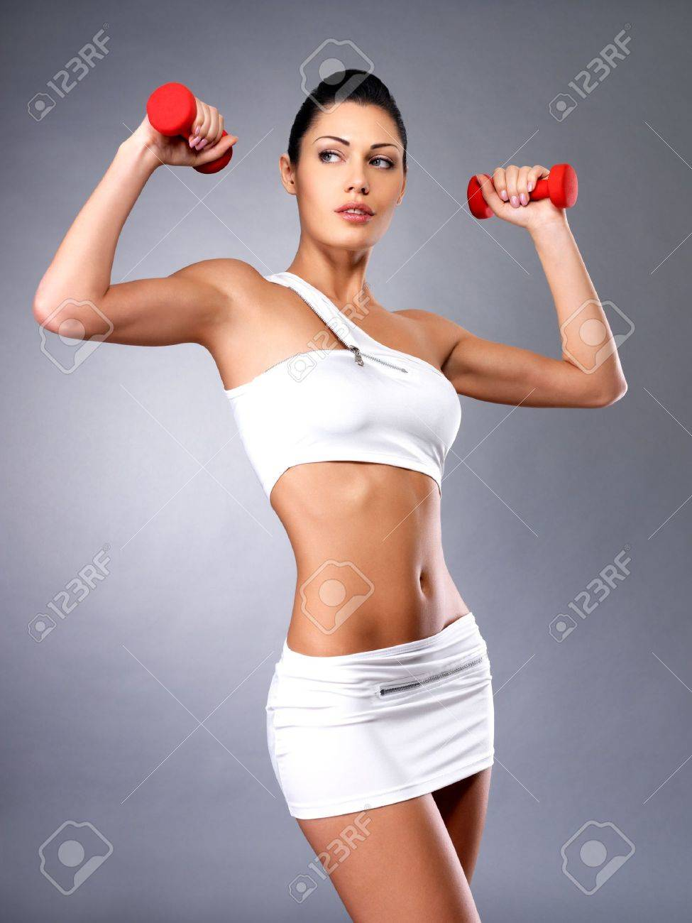 beautiful young woman with dumbbells -  grey studio background. Healthy lifestyle concept. Stock Photo - 16300956