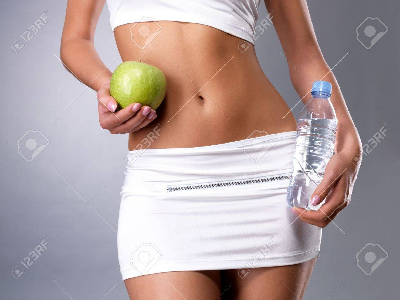 Healthy female body with apple and bottle of water. Healthy fitness and eating lifestyle concept. Stock Photo - 16300954