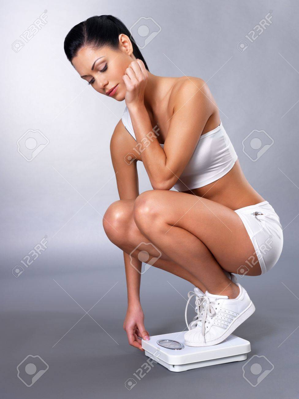 Healthy sports woman stands on the scales and checks her  weight Stock Photo - 16410659