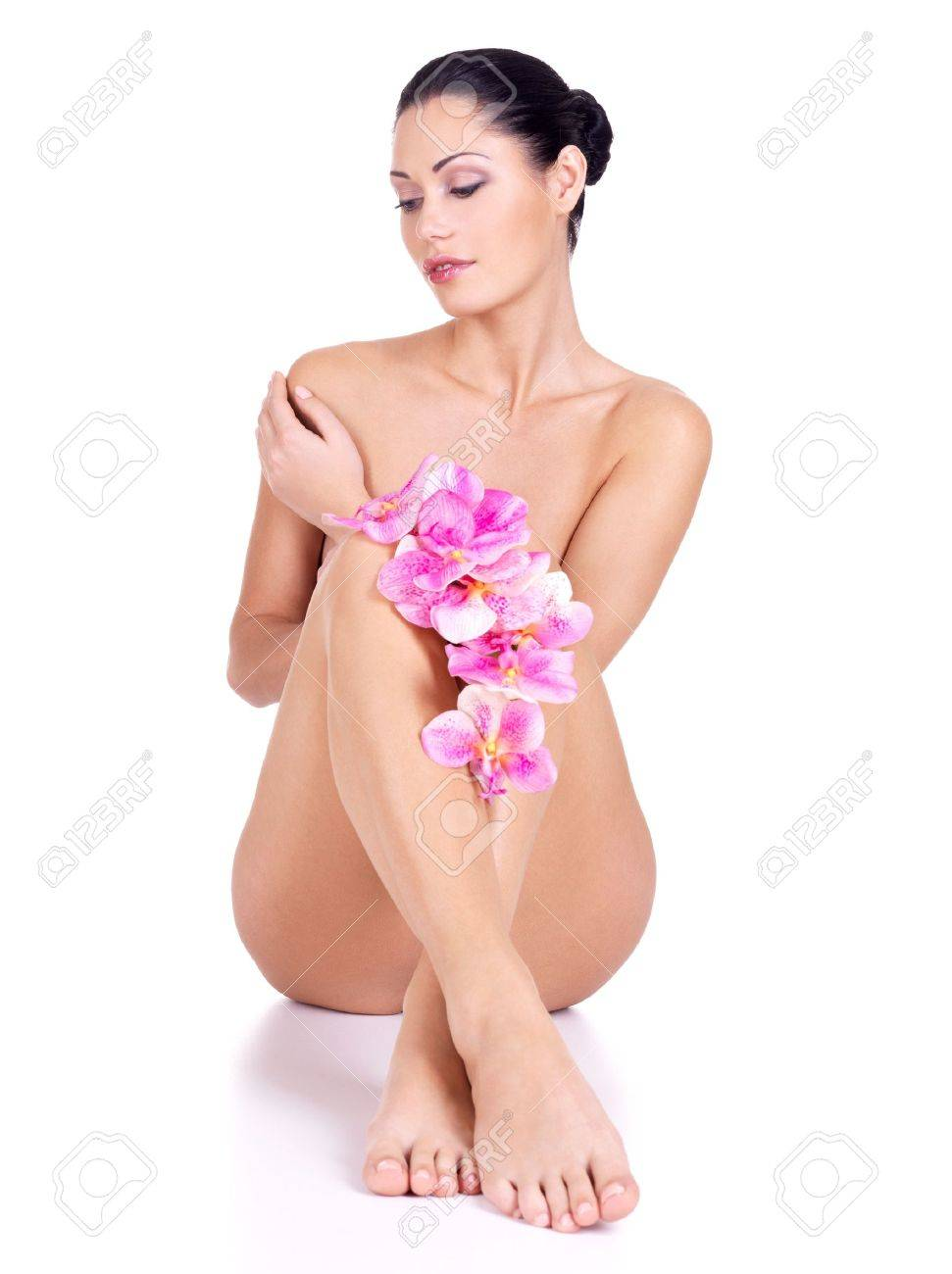 Young woman with nude body sits on the white background with flowers Stock Photo - 16410681