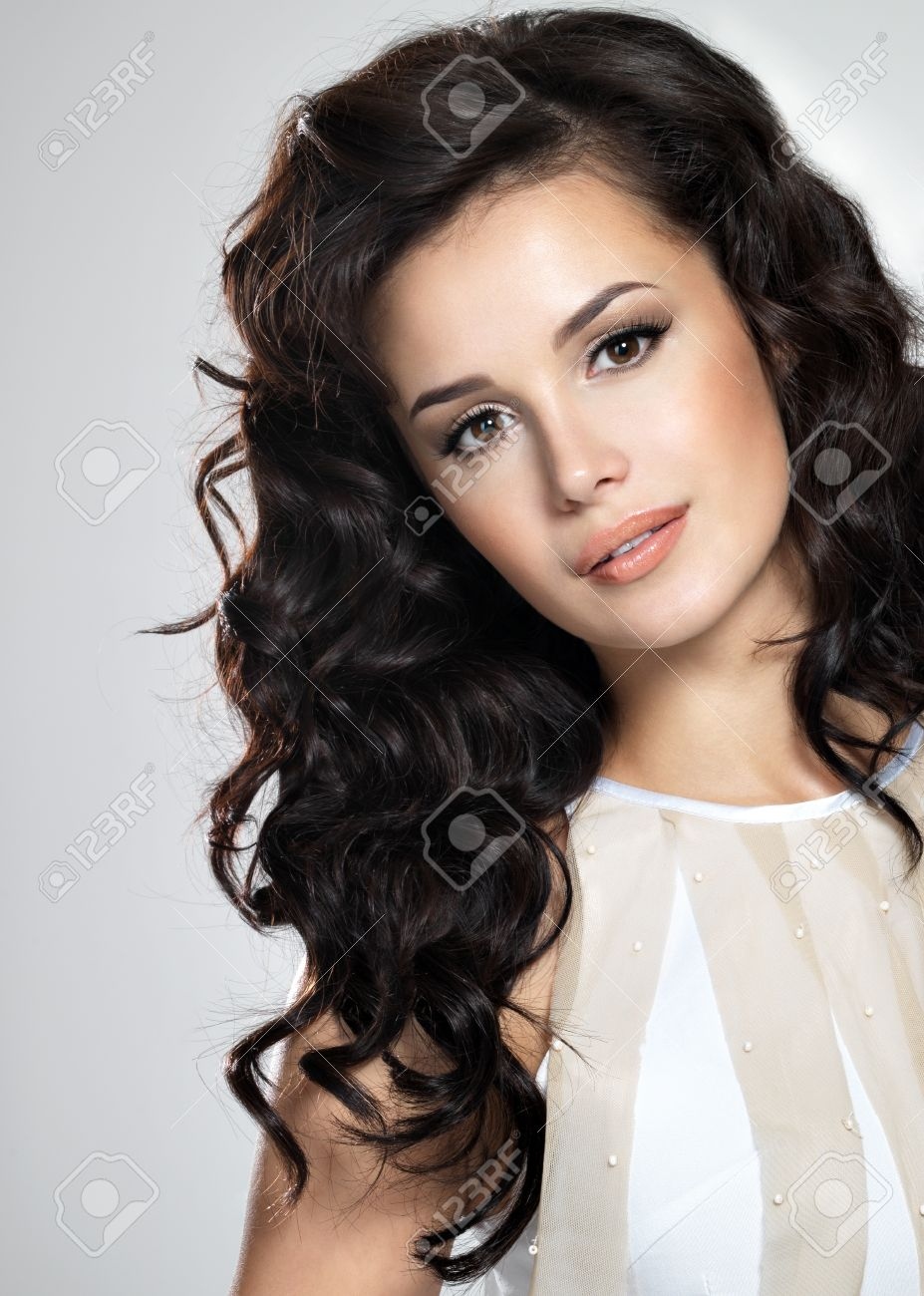 Beautiful brunette model with long curly brown hair. Pretty model poses at studio. Stock Photo - 16444316