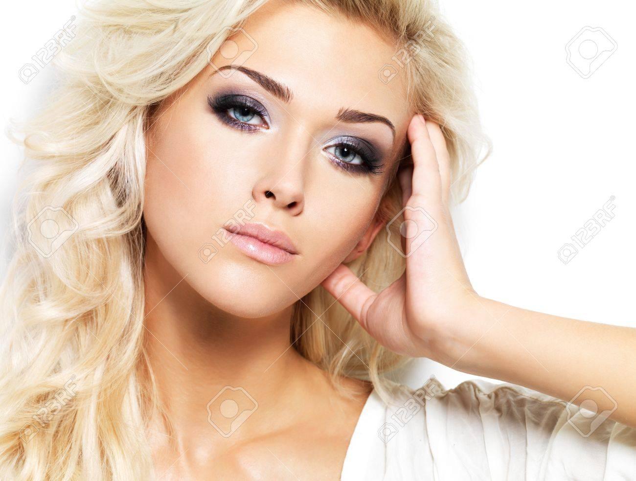 Banque d images - Belle femme blonde aux longs cheveux bouclés et le  maquillage style. Fille posant sur fond blanc e5d94c07853d