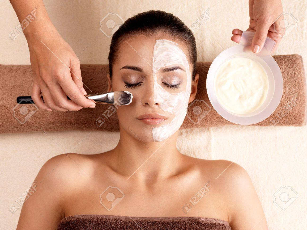 Spa therapy for young woman receiving facial mask at beauty salon - indoors Stock Photo - 16578469