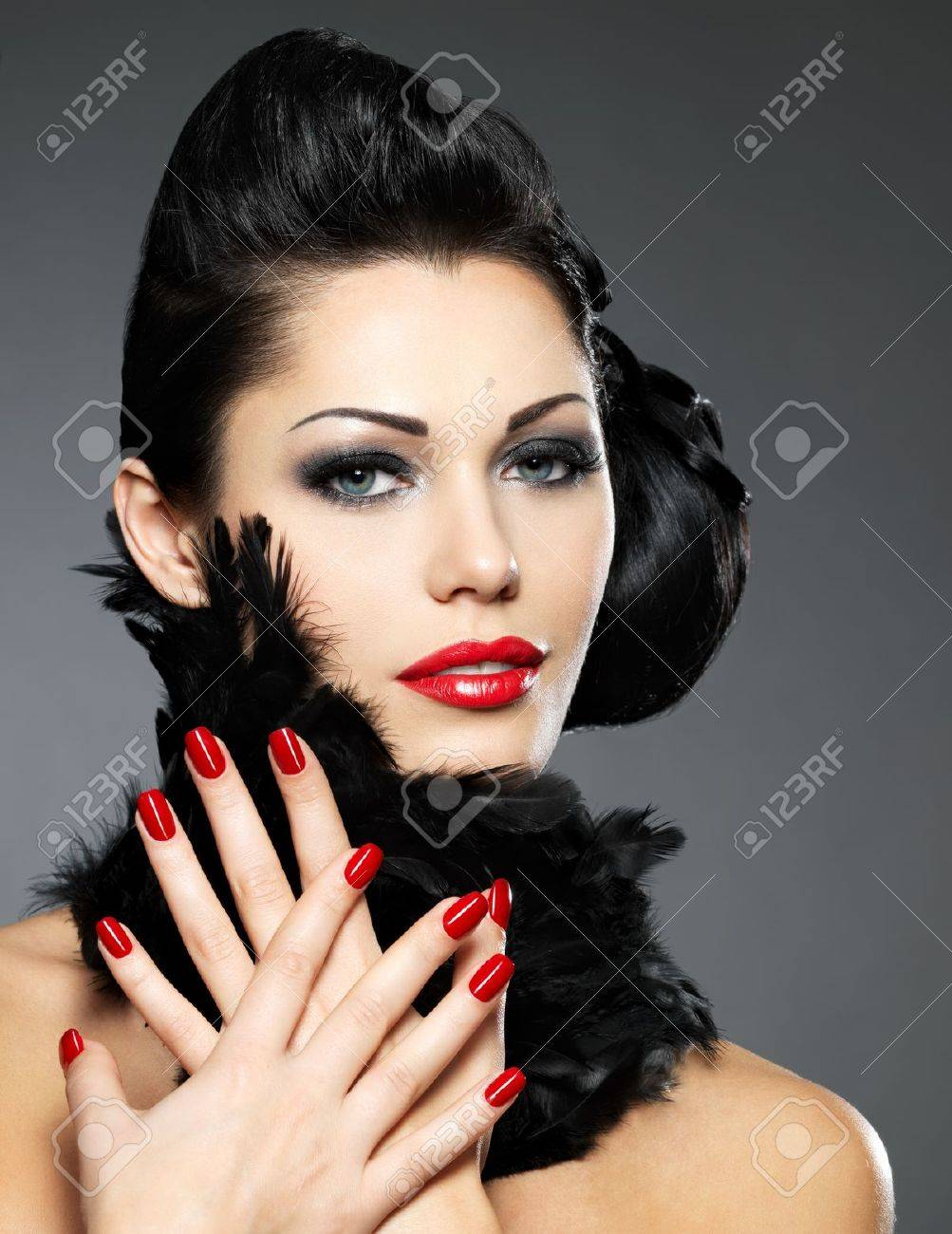 Beautiful fashion woman with red nails, creative hairstyle and makeup - Model posing in studio Stock Photo - 16642944